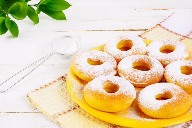 Donuts con azúcar en polvo servido en plato amarillo