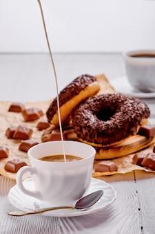 Donuts de chocolate y café en madera brillante.