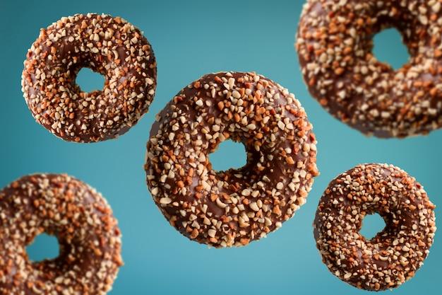 Donuts de chocolate con maní volando sobre fondo azul, concepto de comida chatarra
