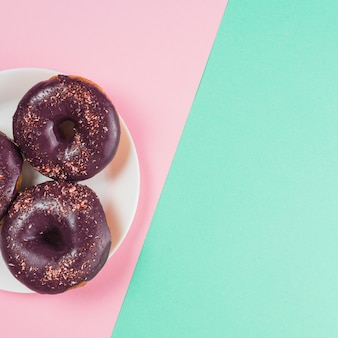 Donuts de chocolate en placa sobre fondo rosa y menta