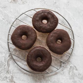 Donuts de chocolate sobre el estante circular de acero inoxidable sobre fondo de mármol