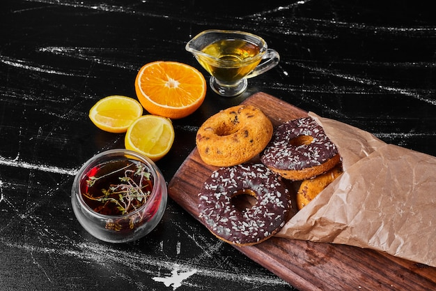 Donuts de chocolate sobre una tabla de madera con té de hierbas