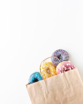 Donuts de colores glaseados en bolsa de papel