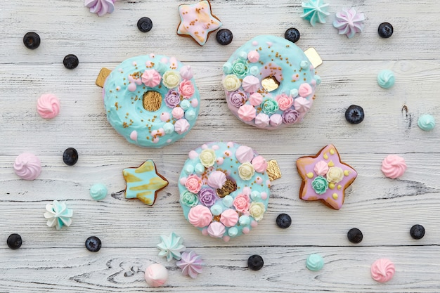 Donuts de colores en la pared de madera blanca
