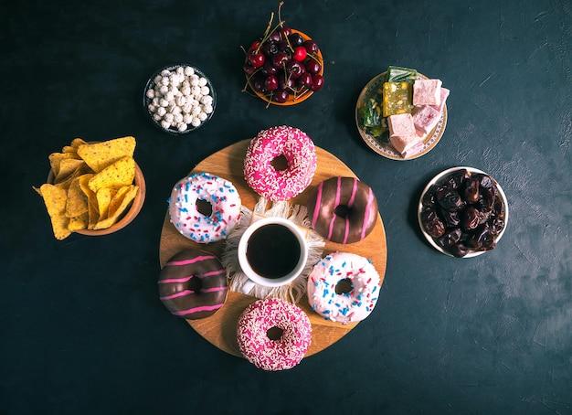 Donuts de colores sobre una mesa negra. vista superior