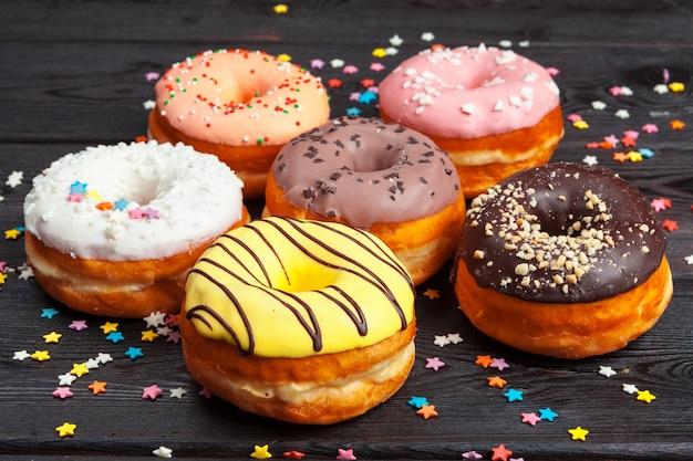 Donuts coloridos decorados con confeti rocía sobre fondo de madera oscura