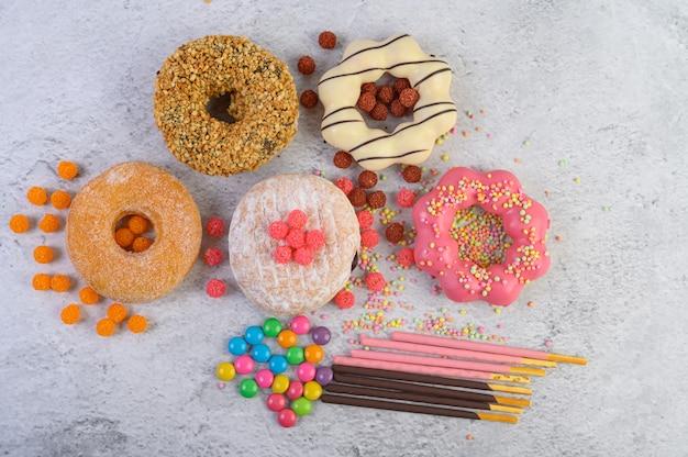 Donuts decorado glaseado y rocía sobre la superficie blanca vista superior