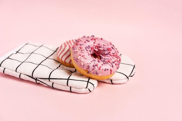 Donuts decorados con glaseado y cobertura se encuentran en el guante del chef en una copia de vista superior de fondo rosa