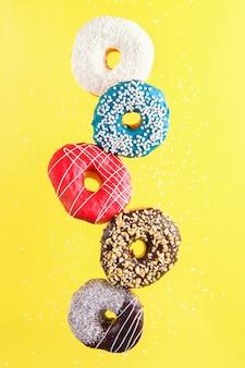 Donuts decorados multicolores en movimiento cayendo