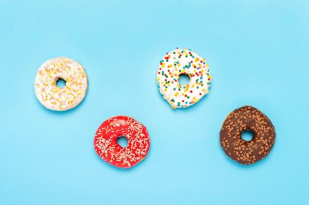 Donuts de diferentes tipos sobre una superficie azul. concepto de dulces, panadería. . vista plana, vista superior
