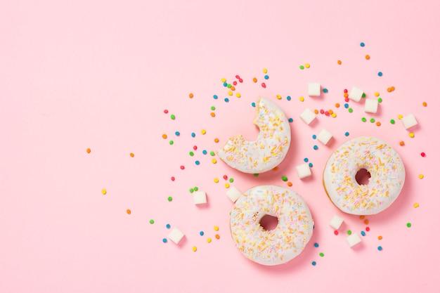 Donuts dulces sabrosos frescos, caramelos decorativos multicolores, terrones de azúcar sobre un fondo rosa. concepto de panadería, pasteles frescos, delicioso desayuno, comida rápida. vista plana, vista superior.