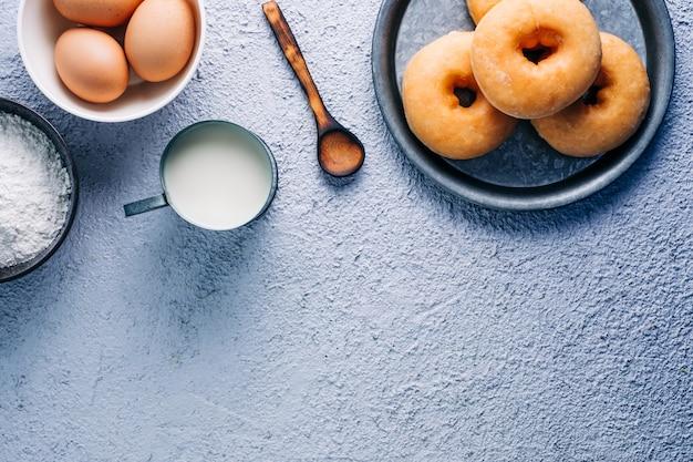 Donuts esmaltados caseros en colores de fondo. ingredientes, leche, huevo, harina. copyspace