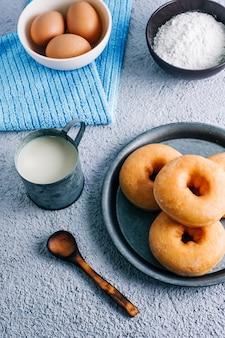 Donuts esmaltados caseros en colores de fondo. ingredientes, leche, huevo, harina.