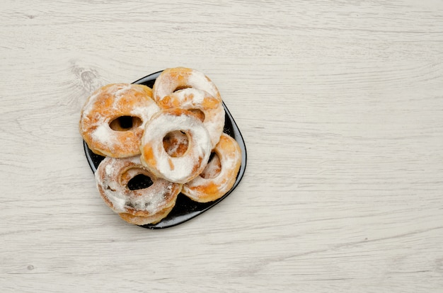 Donuts espolvoreados con azúcar en polvo sobre una luz de madera, con copyspace. vista superior