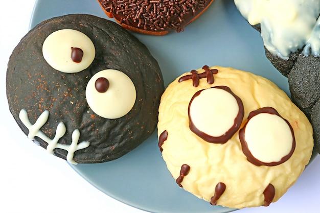Donuts en forma de monstruos en blanco y negro servidos en el plato para halloween