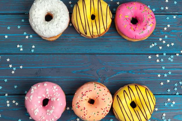 Donuts frescos coloridos en superficie de madera azul oscuro