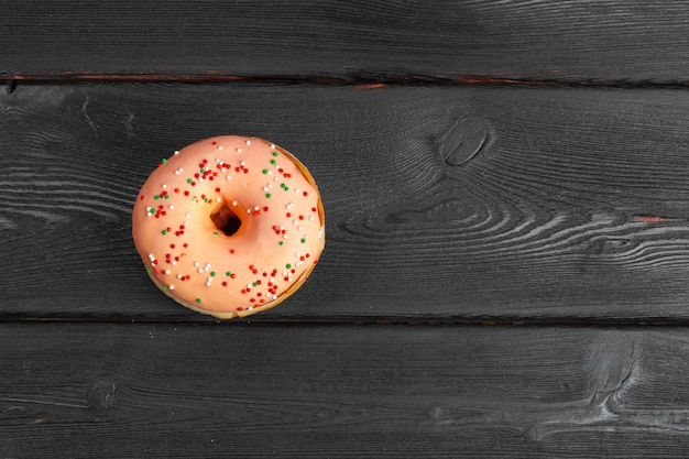 Donuts frescos coloridos en superficie de madera negra oscura