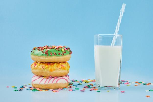 Donuts glaseado rocía con un vaso de leche sobre un fondo azul pastel. donut y leche, concepto de desayuno. de cerca