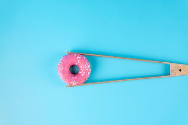 Donuts glaseado sostenido por unas pinzas en azul