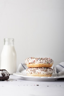 Donuts glaseados apilados con botella de leche y espacio de copia