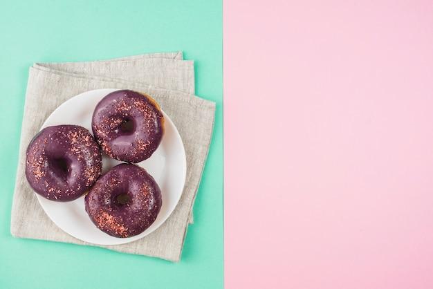 Donuts glaseados de chocolate en placa sobre fondo rosa y menta