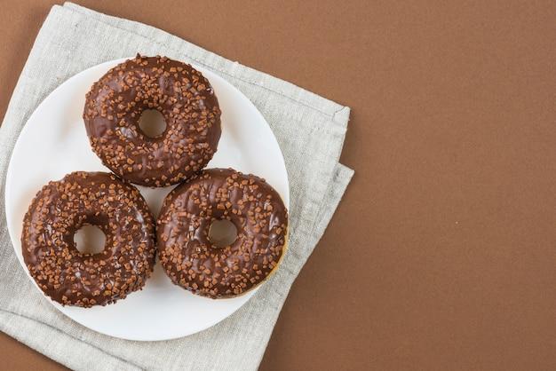 Donuts glaseados chocolate en plato blanco sobre tela gris
