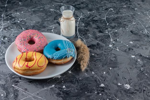 Donuts glaseados coloridos en un plato junto a dos vasos de leche, en la mesa mixta.