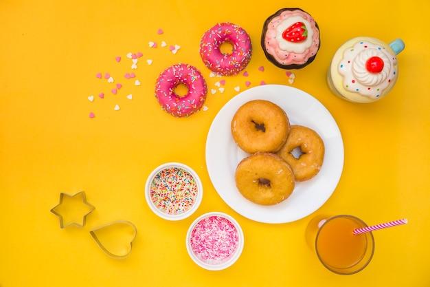 Donuts, jugo, magdalenas y cortador de pastelería sobre fondo amarillo