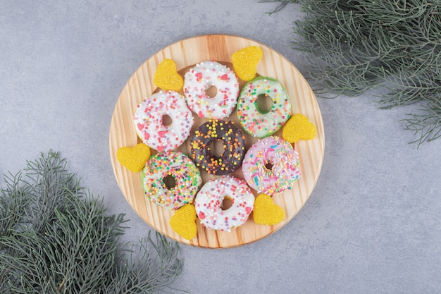 Donuts y mermeladas en un plato junto a ramas de pino en la superficie de mármol