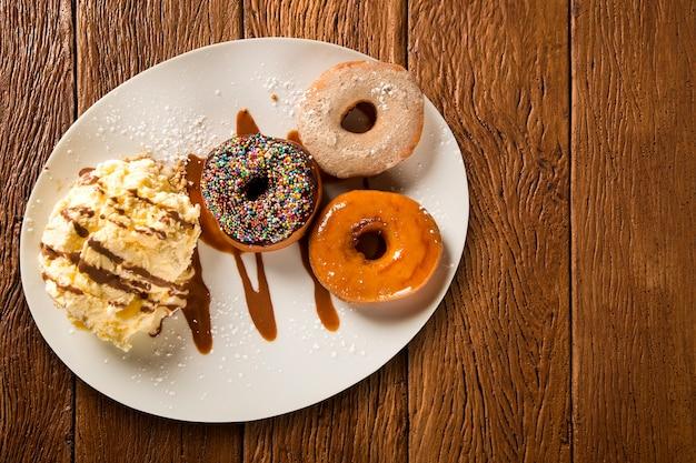 Donuts de postre delicioso con helado en un plato blanco con decoración en una mesa de madera