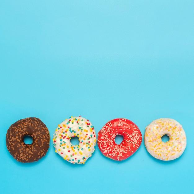 Donuts sabrosos de diferentes tipos en un espacio azul. concepto de dulces, panadería, repostería. cuadrado. vista plana endecha, superior.