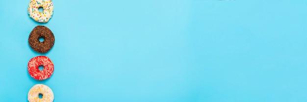 Donuts sabrosos de diferentes tipos sobre una superficie azul. concepto de dulces, panadería, pastelería. . vista plana, vista superior