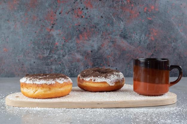 Donuts sabrosos y una taza de té con decoración de copo de nieve, sobre una tabla con polvo de coco espolvoreado sobre superficie de mármol