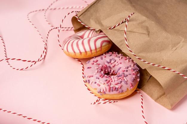 Donuts sobresalen de una bolsa de papel ecológica sobre un fondo rosa