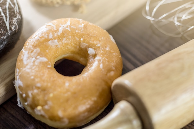 Donuts surtidos con chocolate helado, glaseado rosa y rocía donuts sobre madera de fondo.