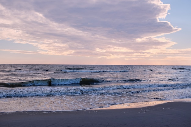 Dorado amanecer detrás de las nubes, cielo rosado y mar en calma. paisaje marino en la noche