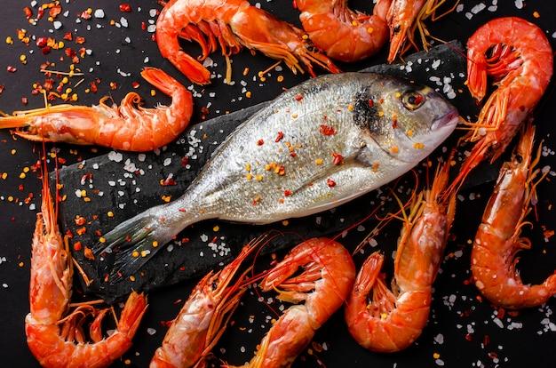 Dorado fresco pescado y langostinos tigre en negro.