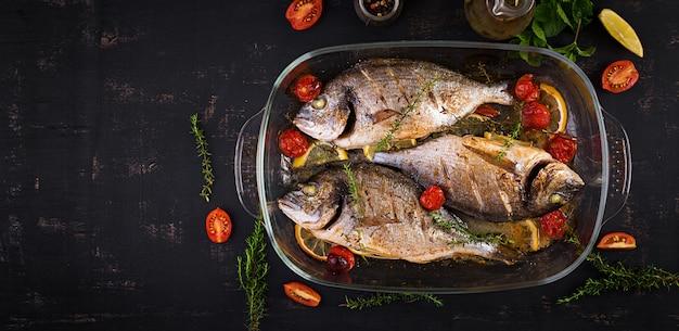Dorado de pescado al horno con limón y hierbas en una bandeja para hornear