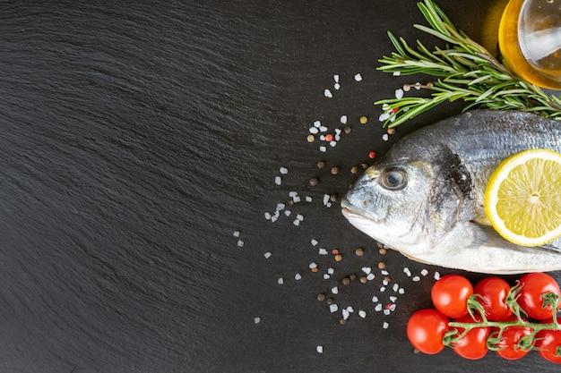 Dorado de pescado crudo sobre fondo de pizarra negra con especias, tomate, romero, aceite de oliva y limón. vista superior, endecha plana con espacio para copiar texto