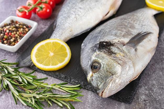 Dorado de pescado crudo sobre tabla de cortar de pizarra negra y fondo de hormigón gris con especias, tomate, romero, aceite de oliva y limón