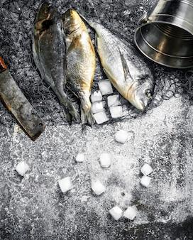 Dorado pescado fresco sin preparar en la tabla de cortar en la mesa rústica.