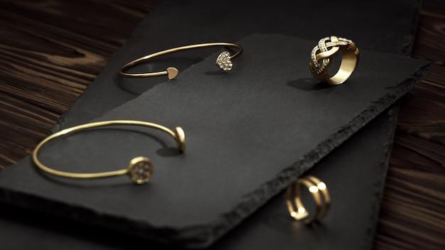 Dorado con pulseras de diamantes y anillos en placas de piedra negra sobre mesa de madera