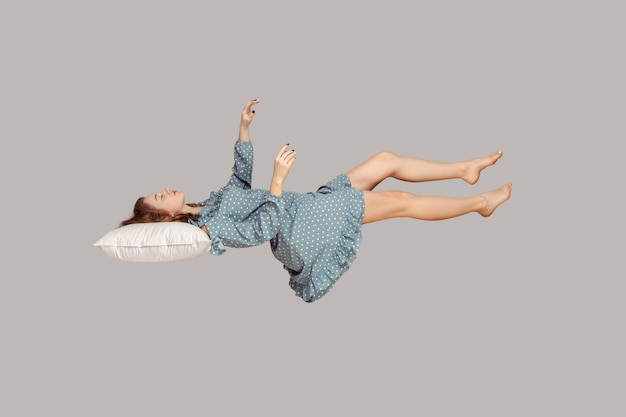 Dormir flotando en el aire. chica relajada manteniendo el ojo cerrado, acostado sobre la almohada levitando