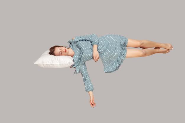 Dormir flotando en el aire. chica relajada en vestido de volantes cómodamente sobre la almohada levitando