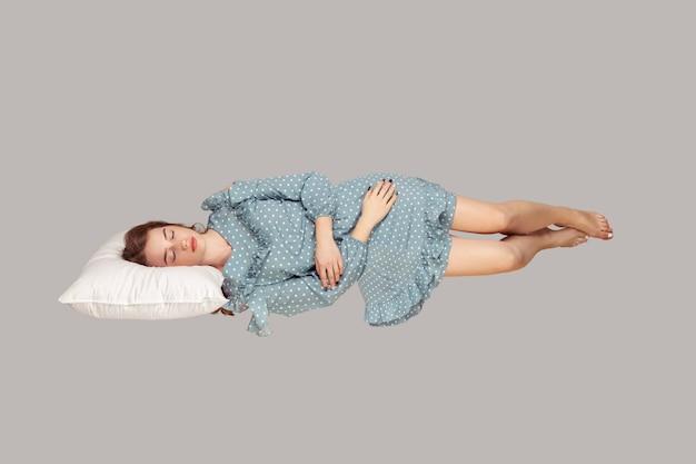 Dormir flotando en el aire. niña acostada cómodamente sobre la almohada levitando