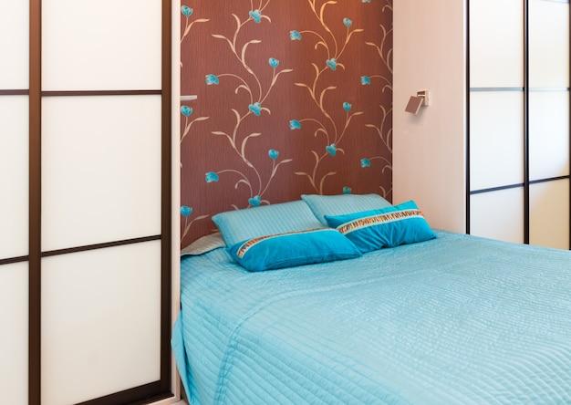 Dormitorio azul y marrón moderno con cama doble de cerca