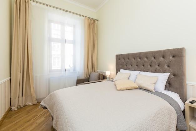 Dormitorio con cama grande, en colores claros
