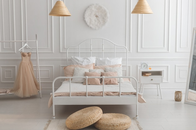 Dormitorio de estilo escandinavo con cama de metal blanco, mesita de noche y pared de color pastel con estuco