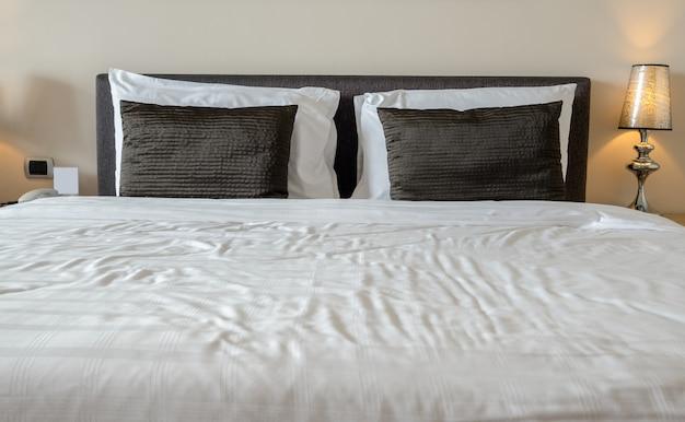 Dormitorio de estilo moderno con almohadas y lámpara.