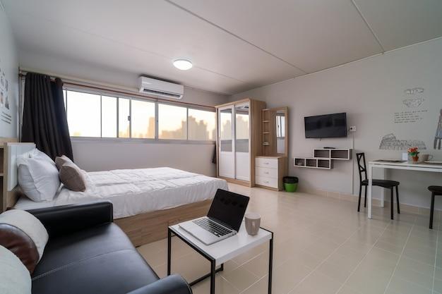 Dormitorio interior con sofá de cuero de la sala de estar y mesa de comedor, tipo de habitación estudio de co